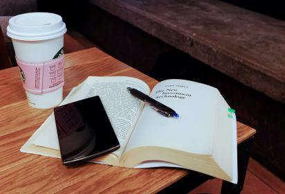 cup book and phone at coffee shop