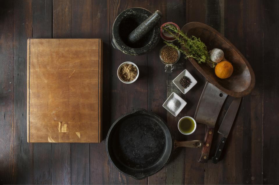 wood, cuttingboard, grinder, spices, pot, castiron, salt, pepper, oil, vegetables, fruit, food, ingredients, butcher knife, knives, garlic, orange