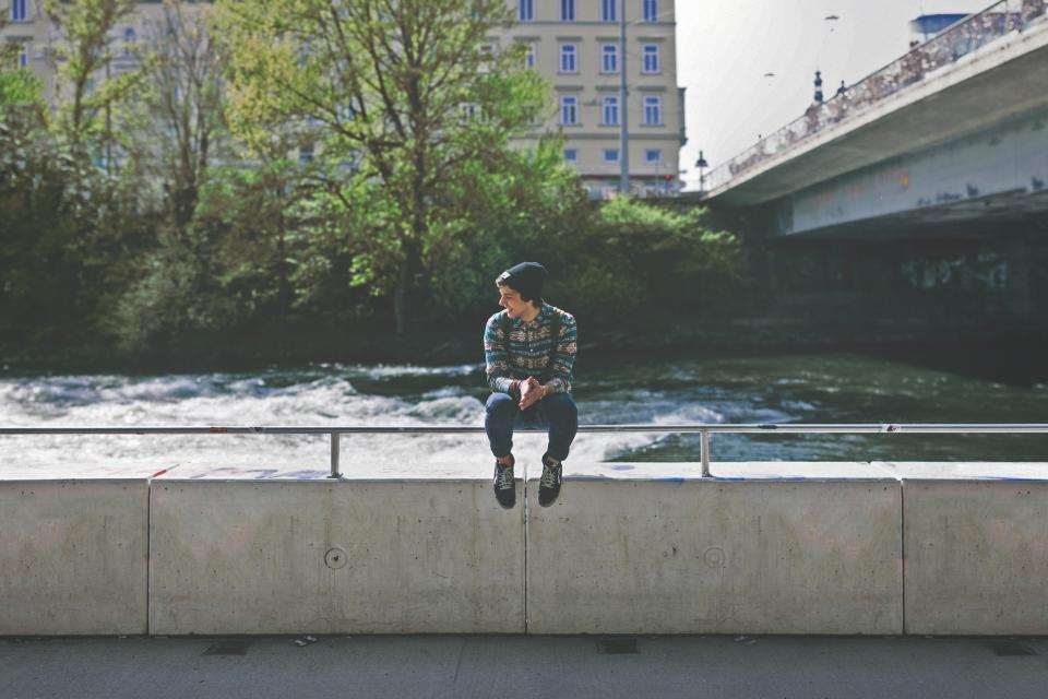 boy, kid, guy, teenager, hat, sitting, water, bridge, tree, city, building, ledge, smile, knapsack, backpack, shoes, jeans, concrete
