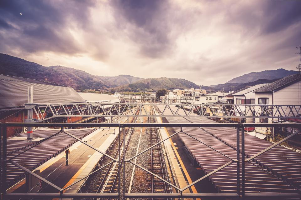 railroad, railway, train tracks, train station, transportation, houses, buildings, city, town, mountains, landscape, nature, sky, clouds, cloudy