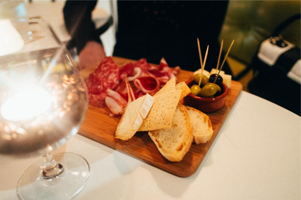 food, appetizers, cutting board, bread, cheese, olives, toothpicks, cured meat, cold cuts, wine, glass, eating