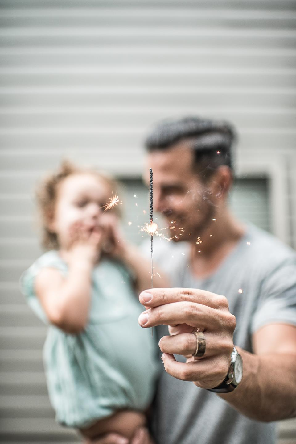 people, parent, man, father, carry, daughter, kid baby, child, hand, stick, sparkle, light, ring, watch, blur