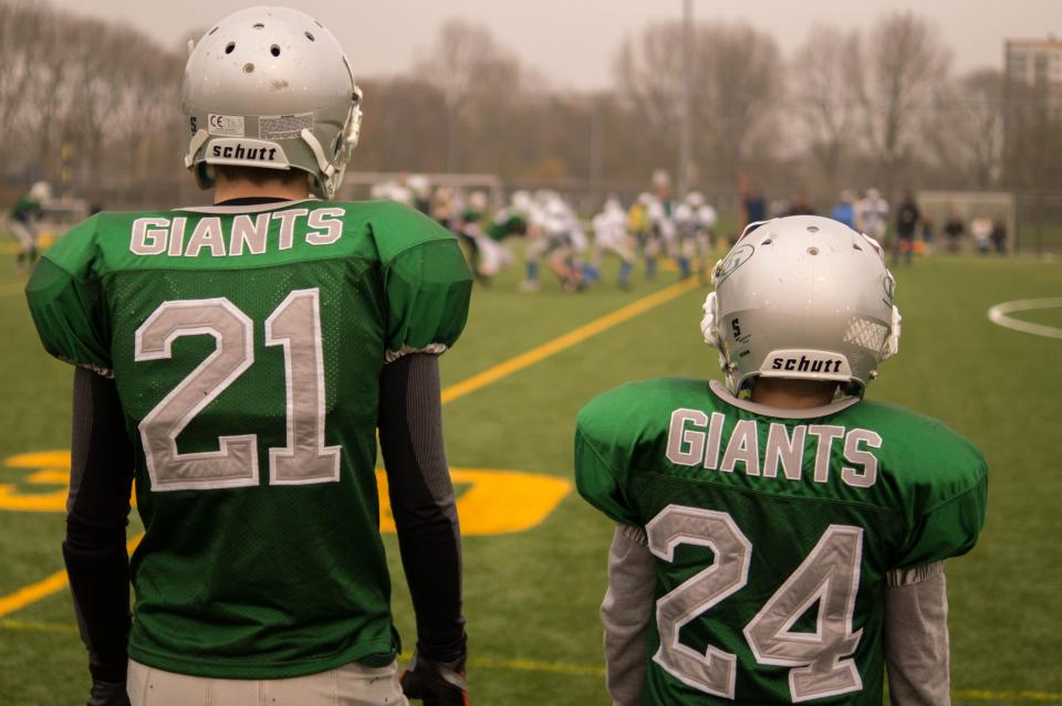 football, teammates, giants, field, sports, athletes, uniform, helmets, green