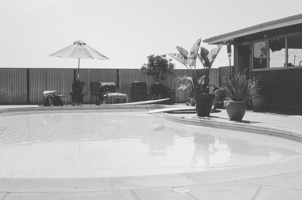 pool, backyard, umbrella, patio, plants, backyard, house, black and white