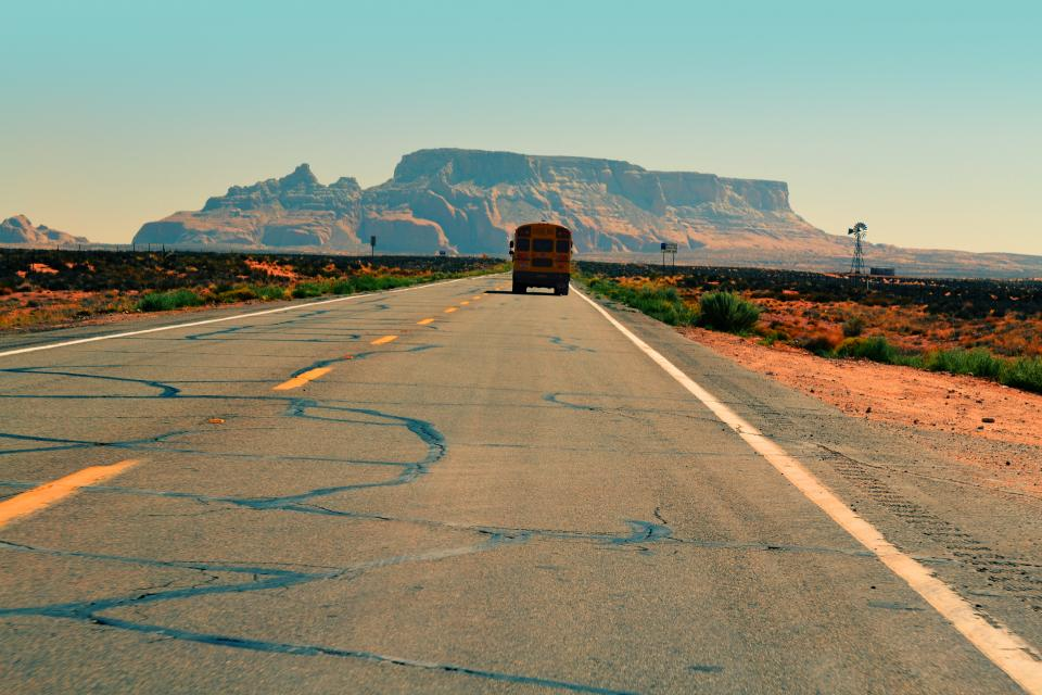 school bus, road, pavement, desert, sand, plants, rural, mountains, cliffs, sunshine, hot