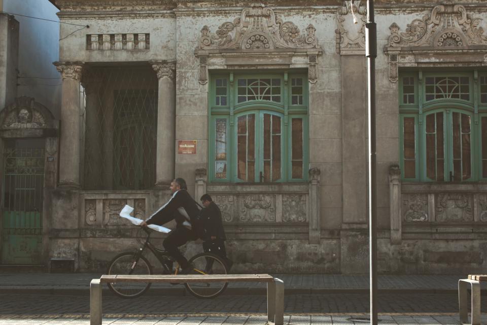 bike, bicycle, biking, man, worker, briefcase, street, cobblestone, building, windows, architecture, stone, bench, post