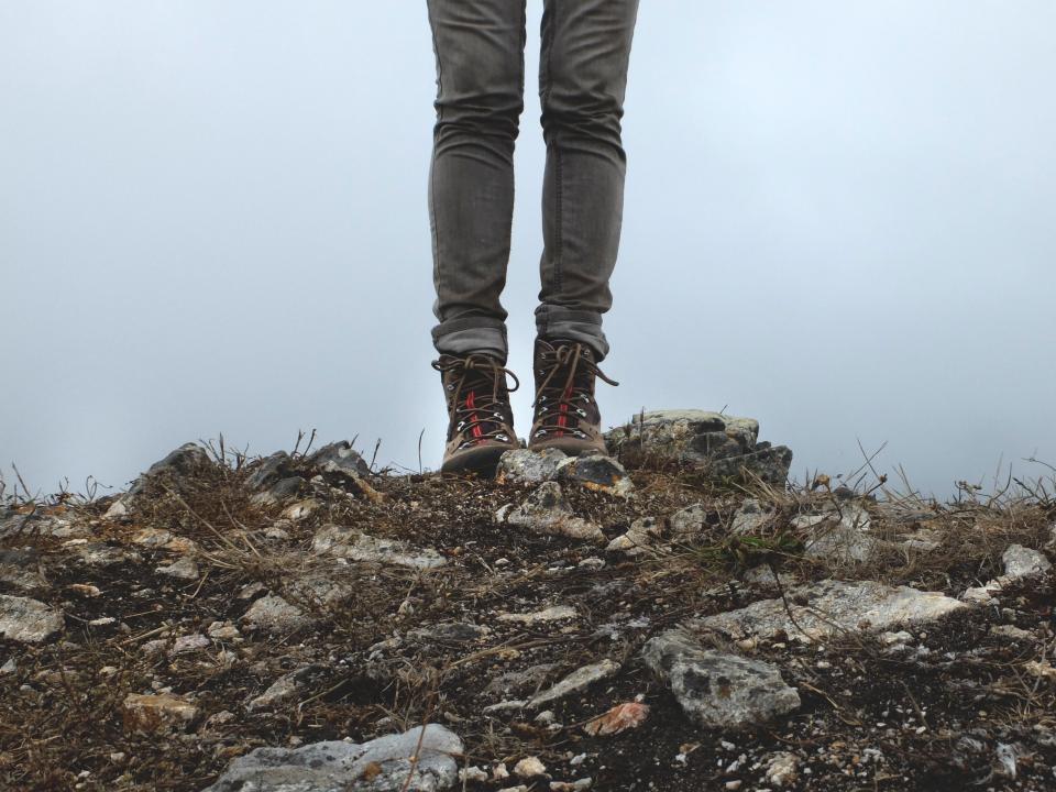 legs, pants, jeans, shoes, boots, laces, rocks, ground, soil, dirt