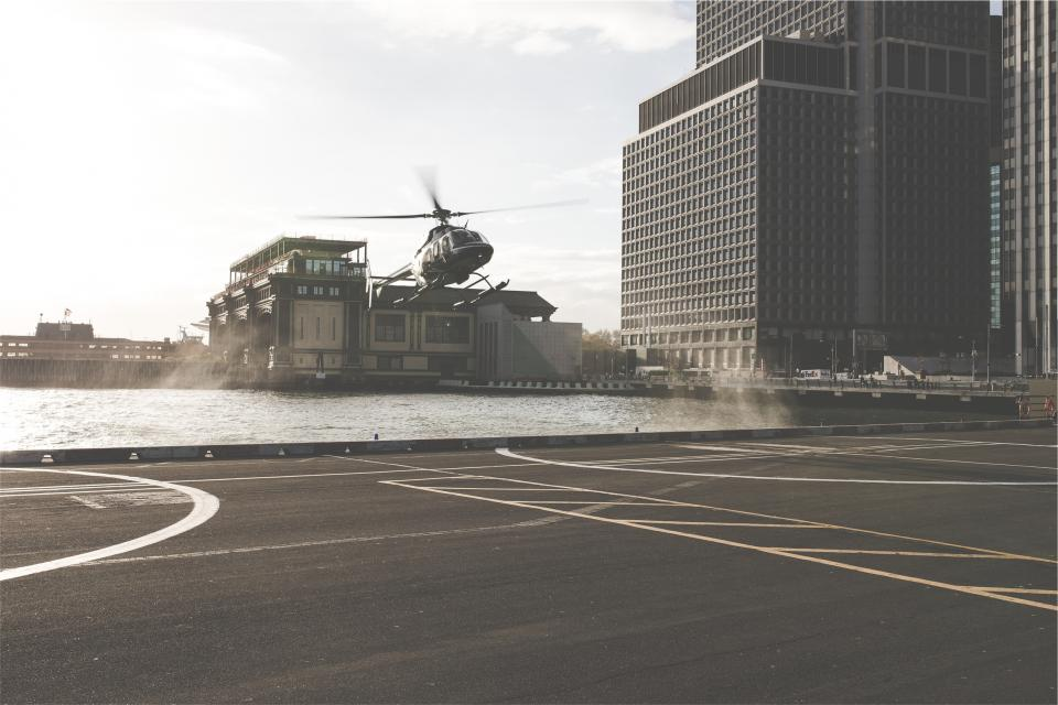helicopter, helipad, pavement, buildings, transportation