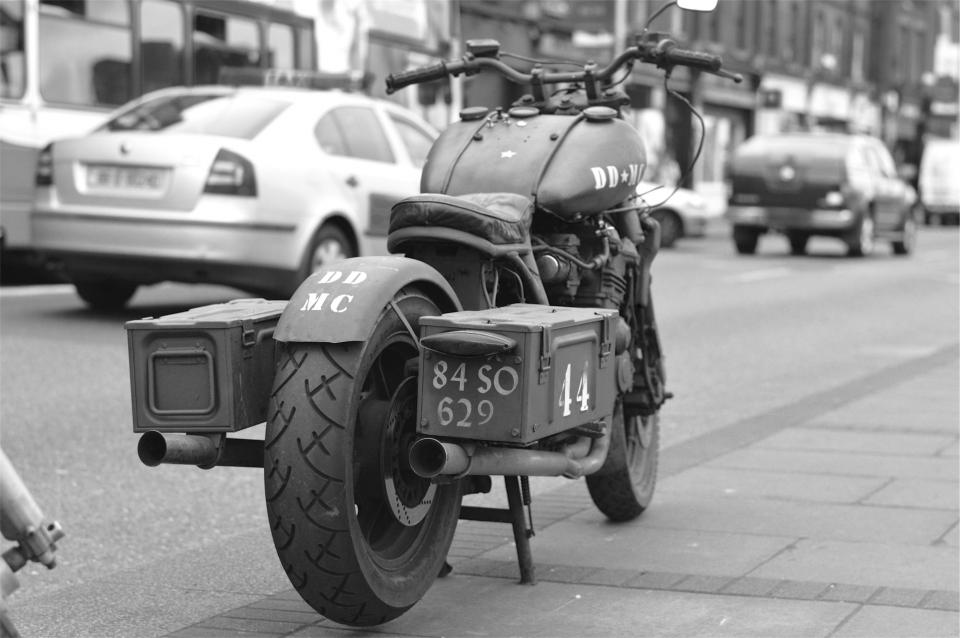 motorcycle, cars, sidewalk, street, road, pavement, black and white