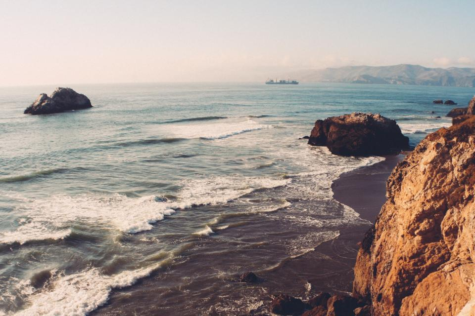 ocean, sea, beach, sand, shore, coast, rocks, boulders, cliffs, mountains, hills, landscape, nature, sunshine, summer, outdoors, sky