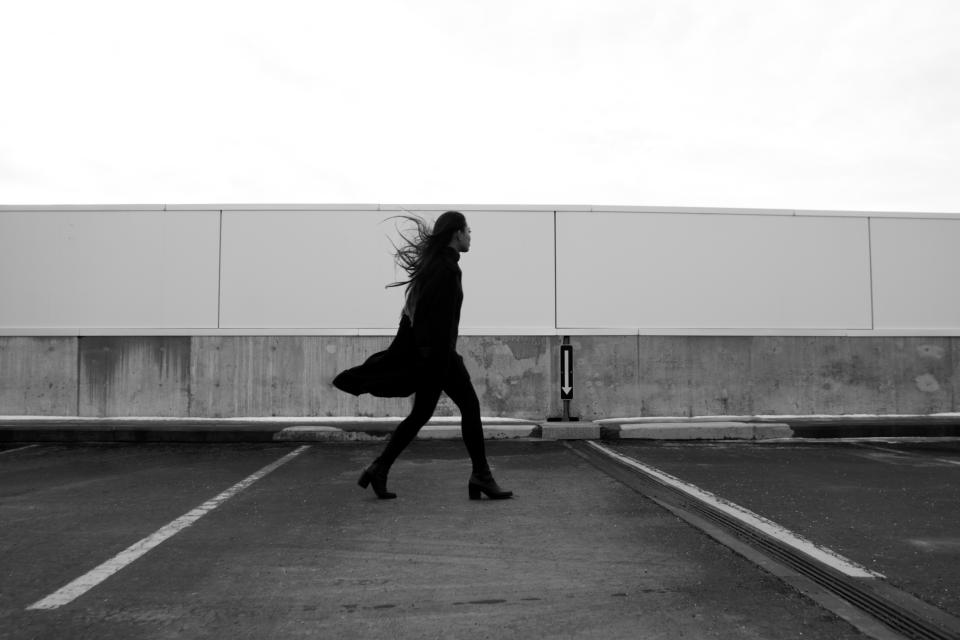girl, woman, model, fashion, coat, boots, heels, windy, parking lot, pavement, black and white, people