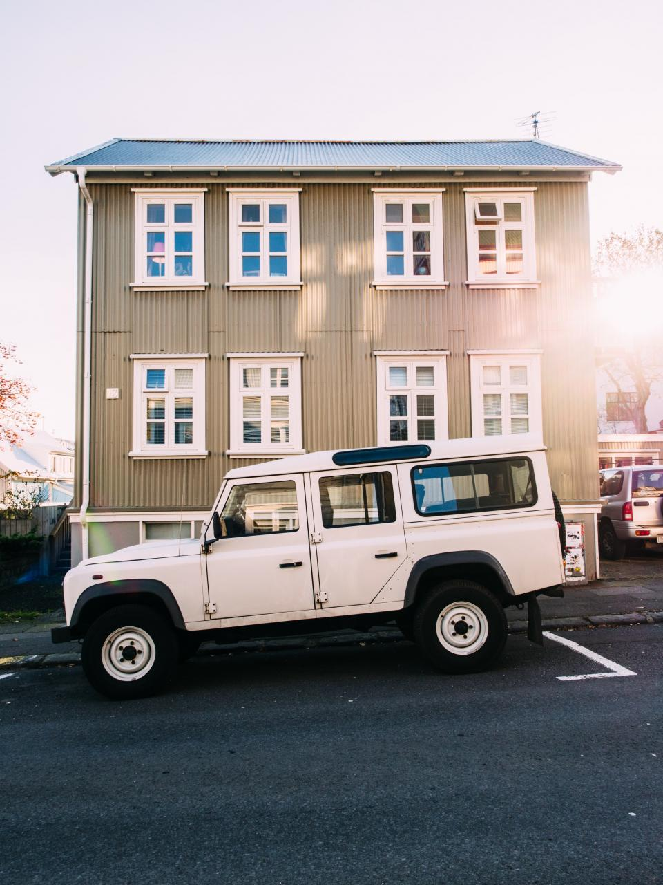 white, suv, truck, hummer, wheels, tires, road, street, sidewalk, building, windows, roof, paneling, house