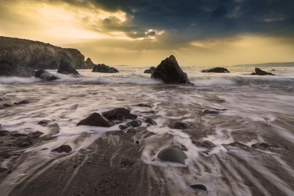 beach, sand, water, waves, splash, rocks, boulders, mountains, cliffs, peaks, sky, sunset, clouds