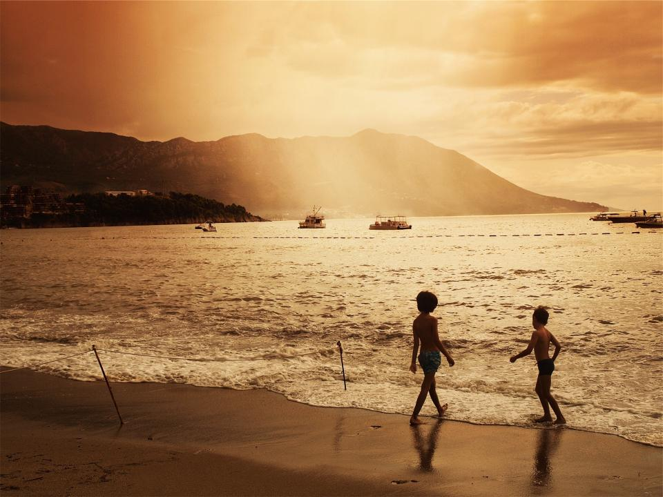 sunset, dusk, beach, sand, waves, water, ocean, sea, boats, ships, kids, children, playing, people, sky, clouds, mountains