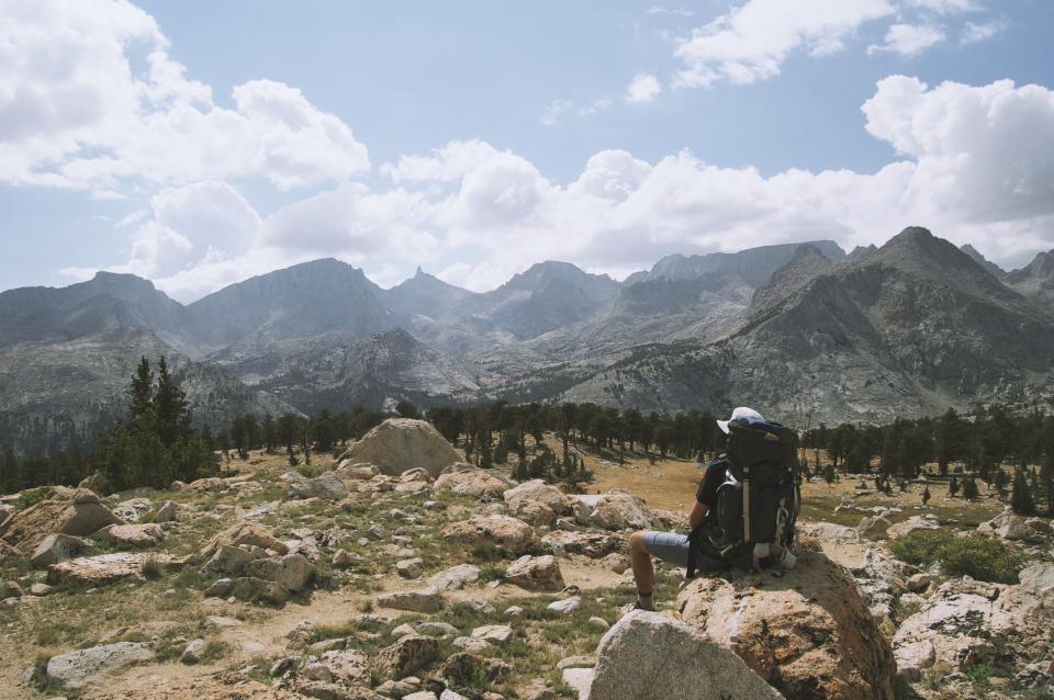 mountains, hiking, hike, trek, knapsack, backpack, outdoors, shorts, hat, trees, boulders, rocks, desert, nature, sunny, sky, clouds