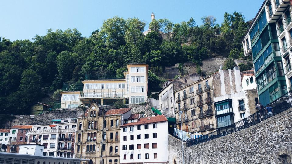 city, town, hills, mountains, buildings, windows, rooftops, stones, trees, statue, balconies, balcony, railing, clock, steps