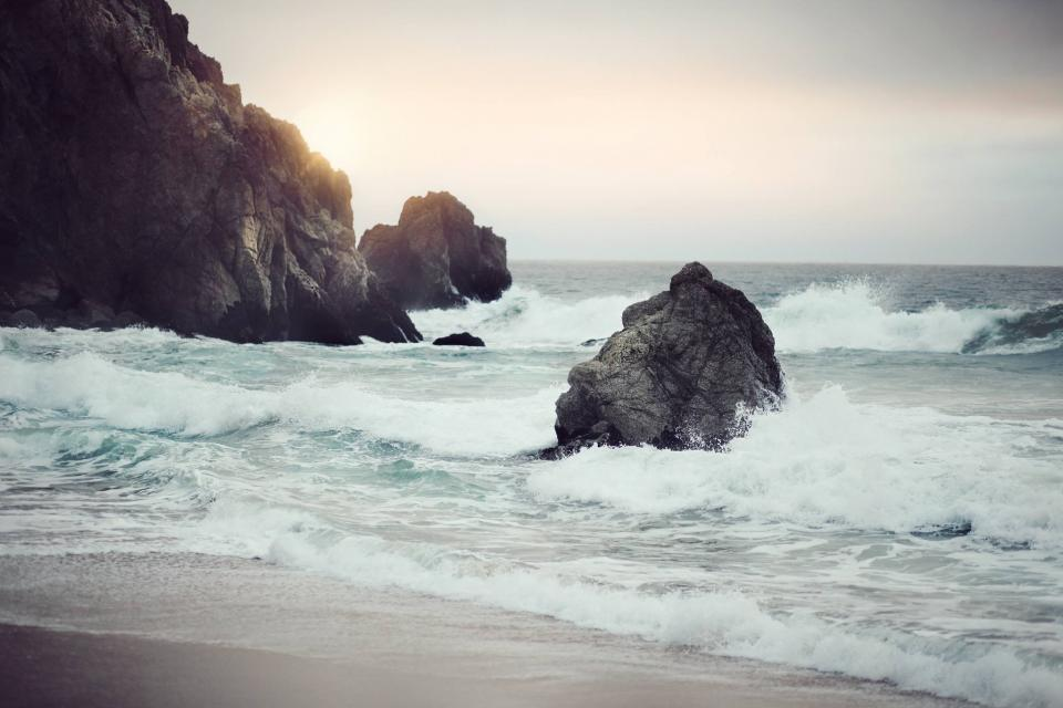 sky, sun, beach, sand, shore, waves, rocks, boulders, water, cliff, ocean, sea