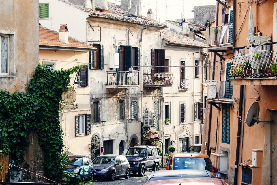 city, town, houses, cars, buildings, balconies, windows, shutters, trucks, hill, street, road, cobblestone
