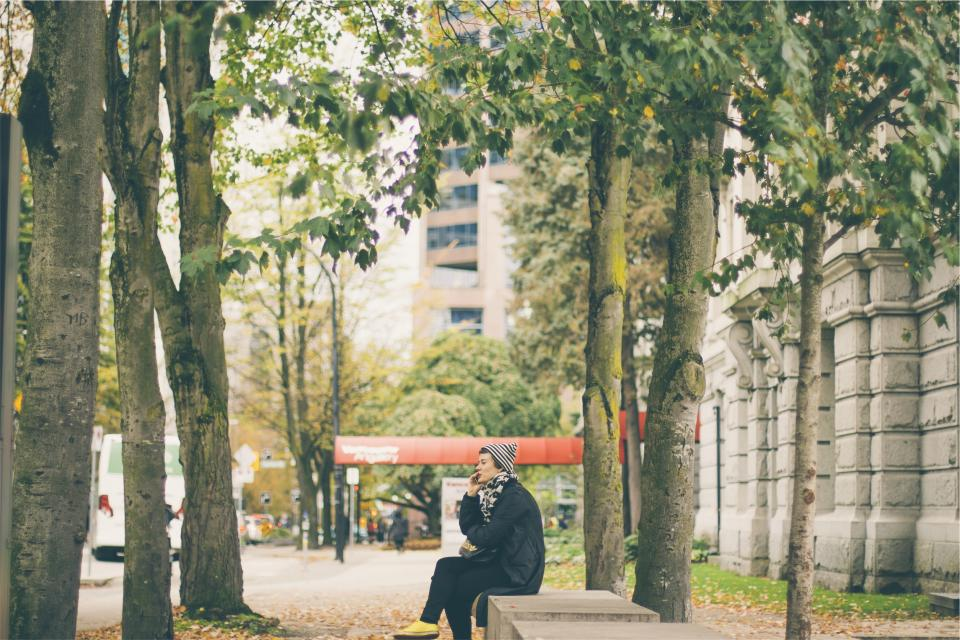 woman, talking, cell phone, bench, sitting, sidewalk, city, hat, jacket, trees, street, people
