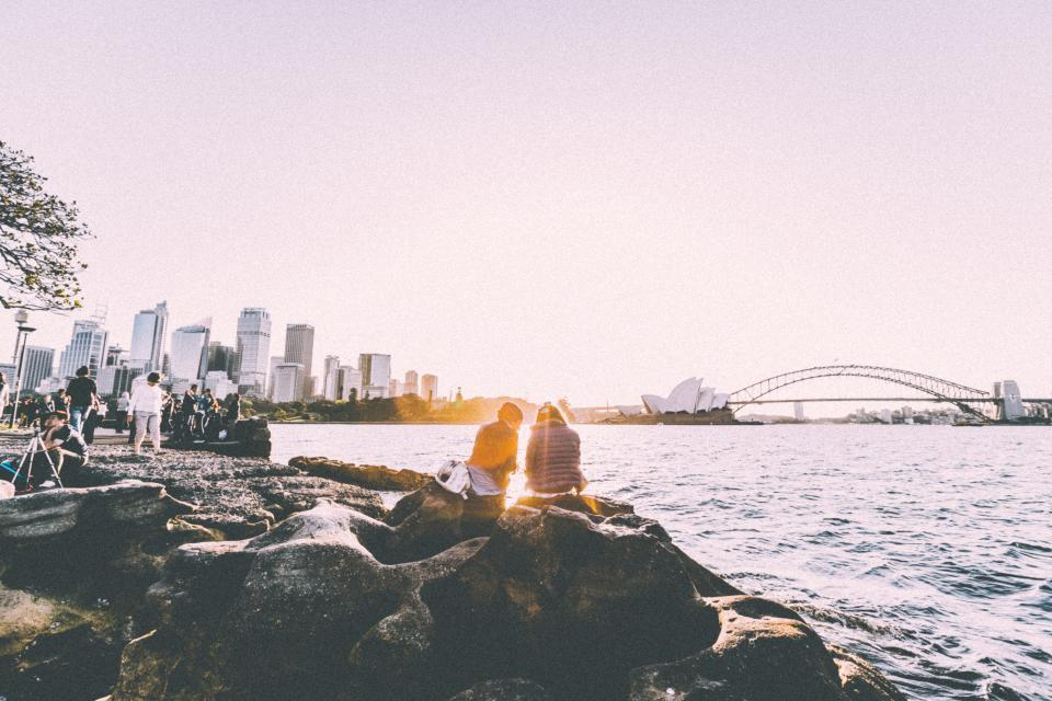 rocks, people, coast, lake, sea, water, city, urban, sunset, buildings, cityscape, skyline, sky, bridge