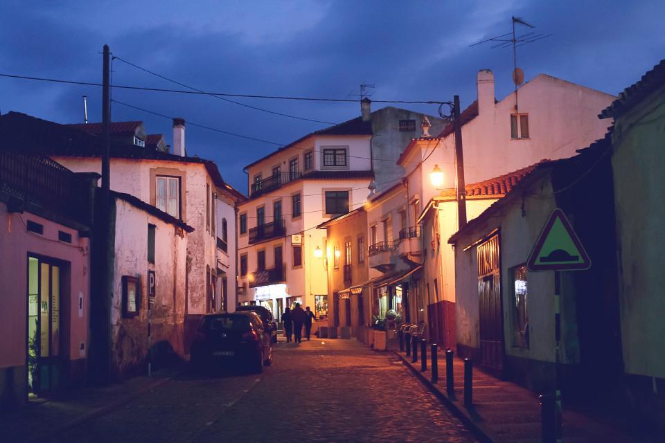 cobblestone, streets, sidewalk, buildings, shops, stores, houses, apartments, city, town, village, people, walking, pedestrians, night, dark, lights, cars, evening