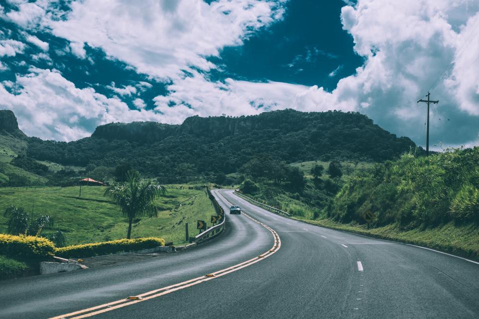 road, highway, cars, driving, green, grass, fields, mountains, hills, sunshine, sky, clouds, outdoors, pavement