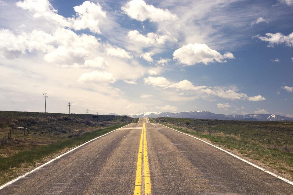 road, pavement, highway, grass, sky, clouds, sunshine, horizon, mountains, peaks, valleys, country