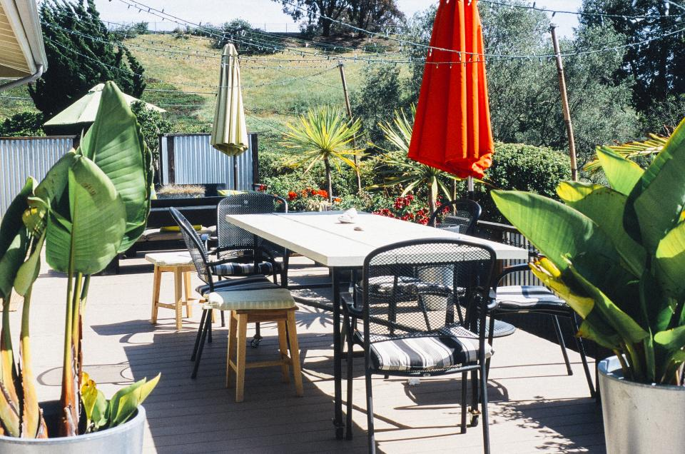 patio, furniture, umbrellas, tables, chairs, plants, wood, deck, backyard, outdoors, sunny, string lights