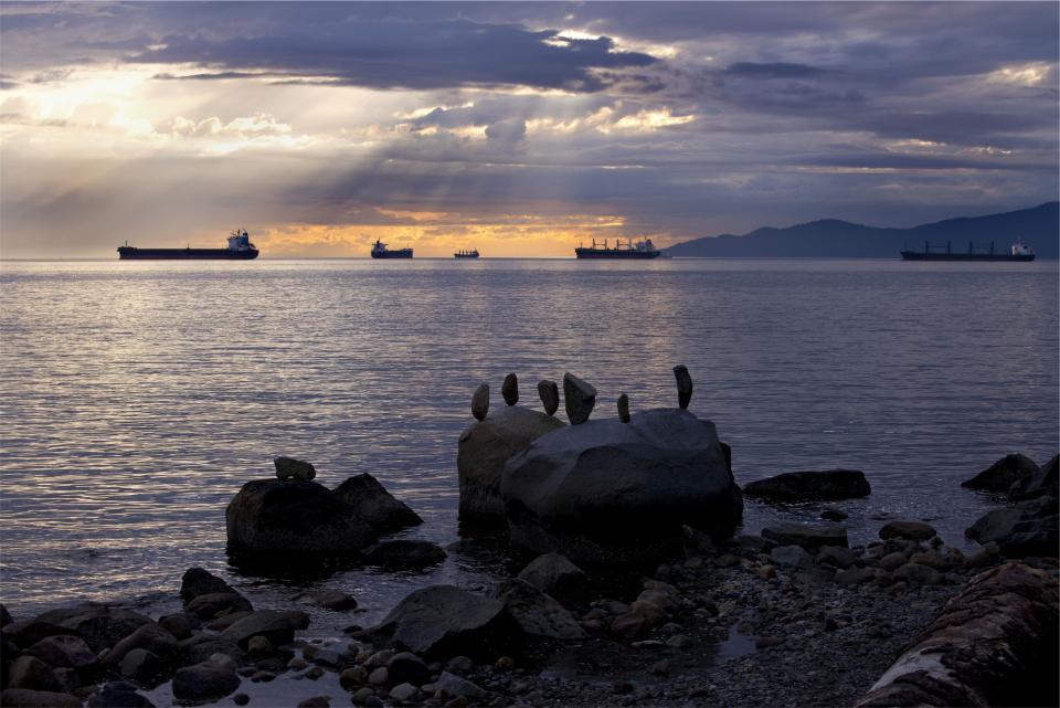 boats, ships, sunset, dusk, sun rays, sky, clouds, water, ocean, sea, shore, rocks, boulders