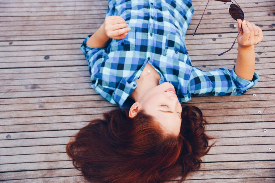 girl, woman, smile, smiling, happy, people, brunette, long hair, plaid, shirt, fashion, clothes, sunglasses, wood, deck, outdoors, lying down