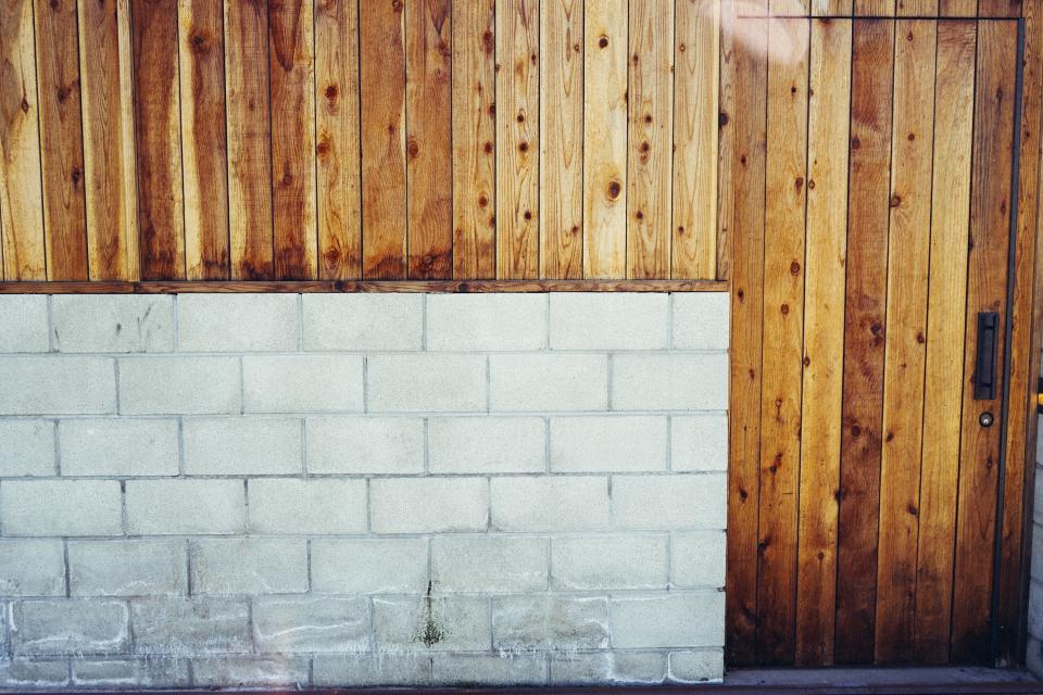 concrete, cinder blocks, wood paneling, door, handle, keyhole, wall
