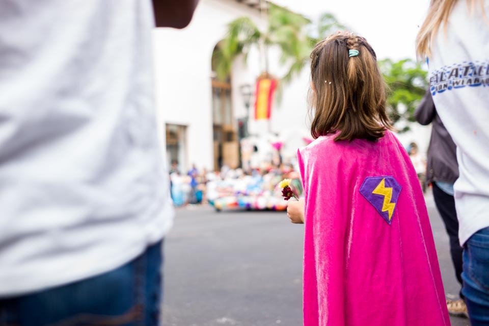 young, girl, pink, cape, lightning bolt, parade, street