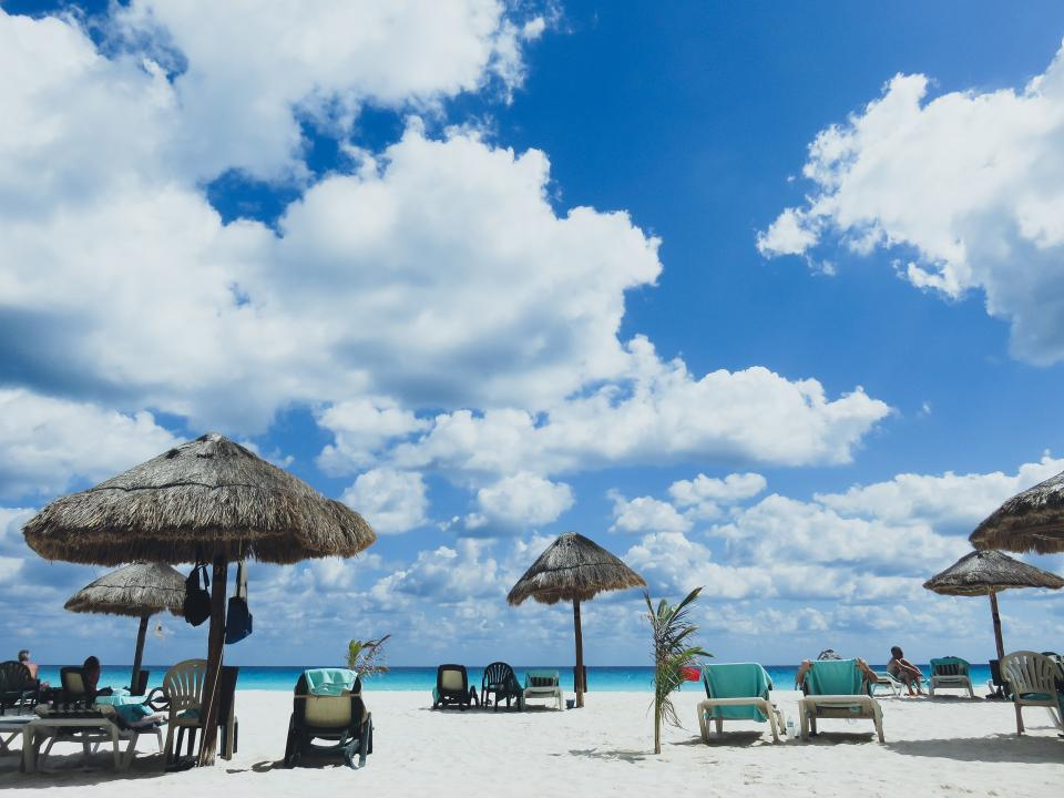 beach, sand, umbrellas, lounge chairs, people, tropical, travel, vacation, blue, sky, clouds, ocean, sea
