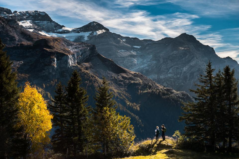 sky, clouds, mountains, peak, snow, hiking, hike, trek, outdoors, nature, man, woman, knapsack, backpack, trail, trees, sunlight, woods
