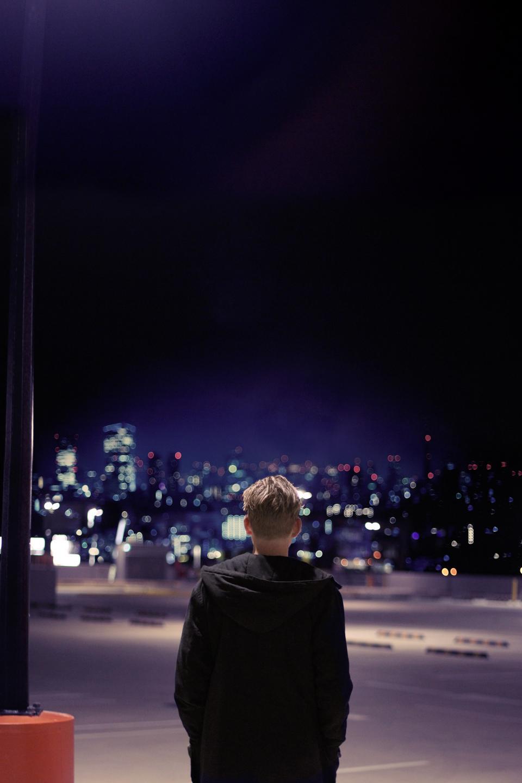 people, man, alone, parking lot, car park, sad, dark, night, city, urban, photography, bokeh, lights, black, hoodie