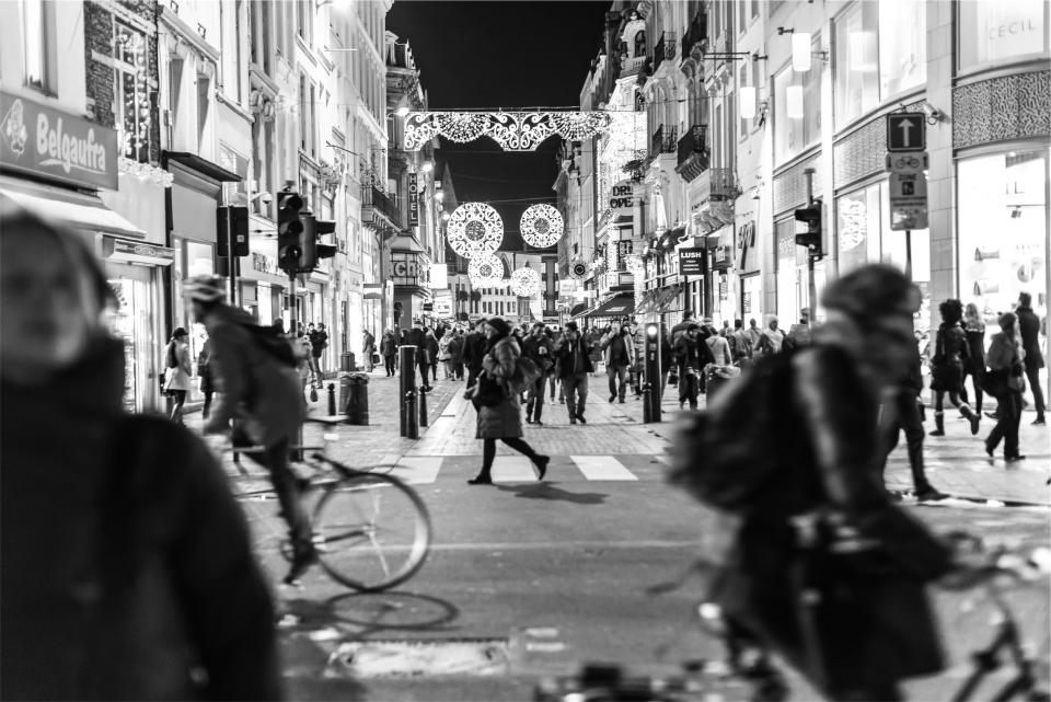 people, crowd, busy, streets, crosswalk, buildings, city, architecture, stores, shops, pedestrians, walking, biking, bike, bicycle, black and white, night, dark, signs, light, evening