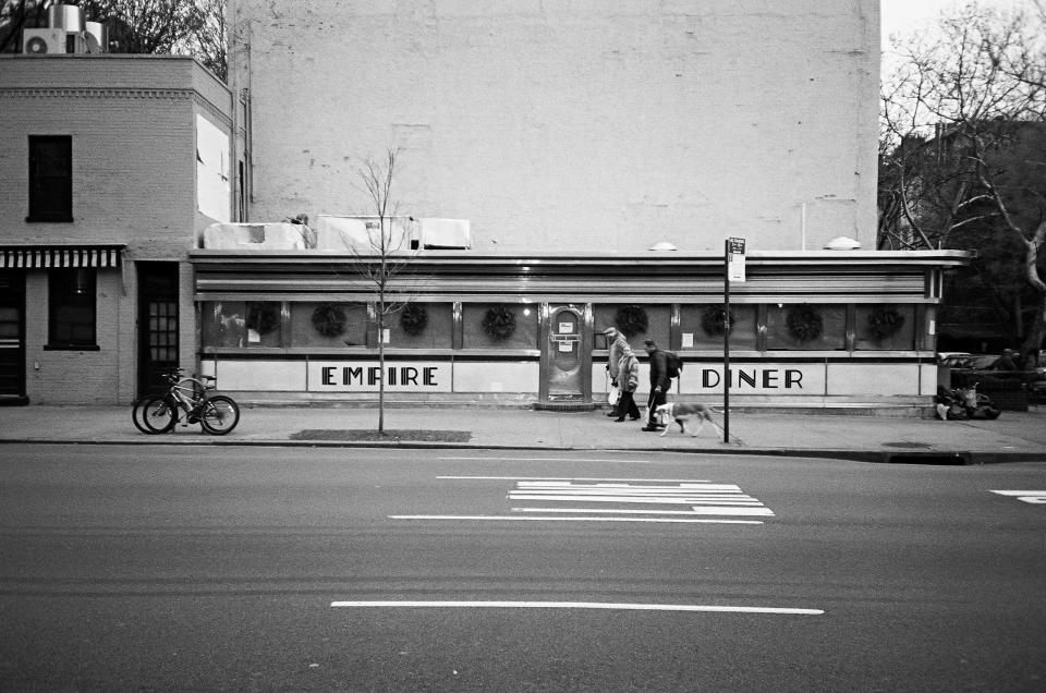 restaurant, diner, food, buildings, road, street, bikes, bicycles, bus stop, dog, animal, walking, pedestrians, people, black and white, city