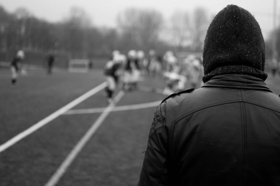 football, field, sports, athletes, spectator, leather jacket, hat, toque, beanie