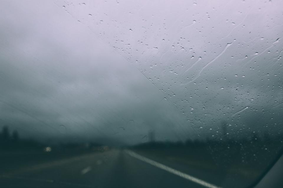 windshield, car, driving, highway, road, raining, rain drops, wet, sky, clouds, cloudy, storm, blurry
