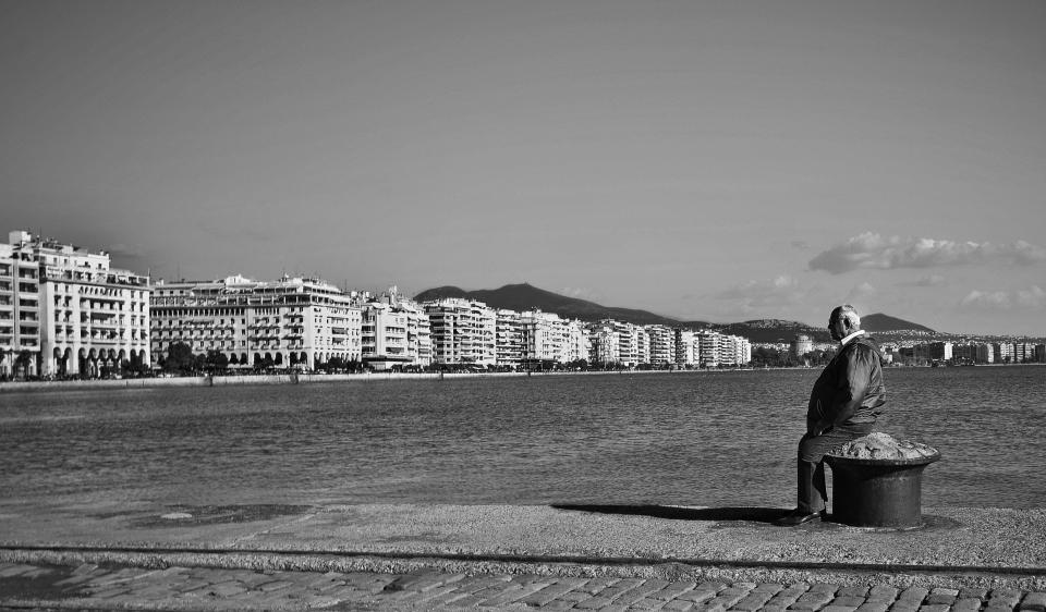 greece, buildings, boardwalk, cobblestone, bay, water, old, man, elderly, sitting, sky, city, town