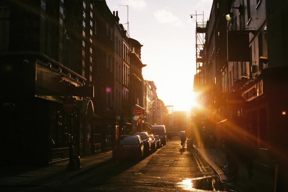 sunset, city, buildings, windows, road, street, cars, cobblestone, people, walking, puddle, stores, shops, signs, sunrays, sunlight, windows