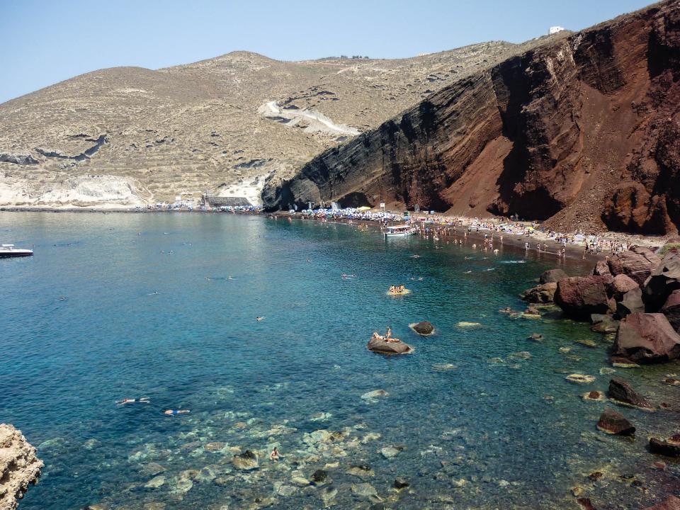 Red Beach, Santorini, Greece, water, sand, people, swimming, boats, rocks, hills, cliffs, people, crowd