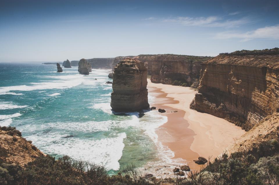 beach, sand, shore, coast, ocean, sea, water, waves, sunshine, sunny, summer, cliffs, rocks, boulders, blue, sky