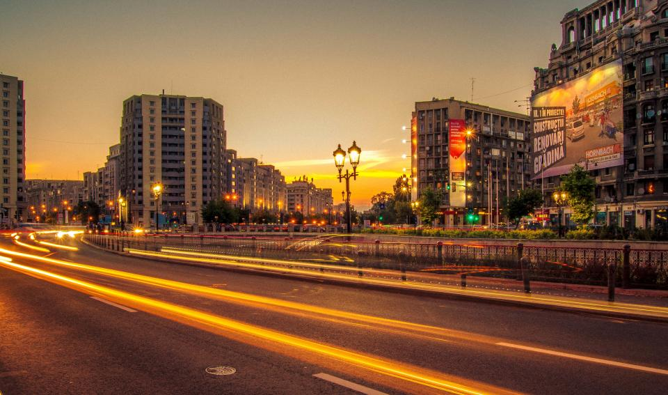 city, buildings, road, street, cars, lights, sunset, dusk, lamp posts, railing, billboards, signs