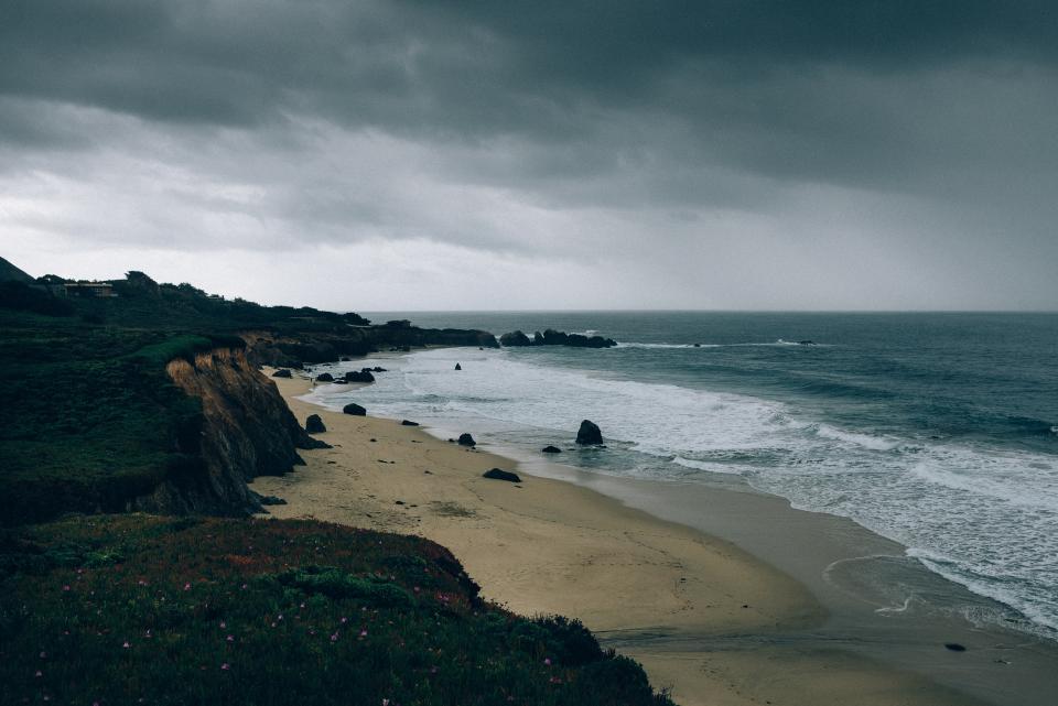 dark, cloudy, storm, ocean, sand, waves, water, shore, mountains, rocks, grass, flowers, plants