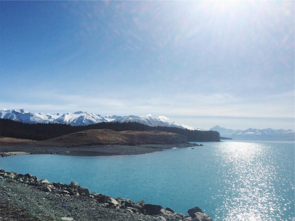 landscape, mountains, peaks, hills, snow, trees, forest, lake, water, sand, rocks, pebbles, sunshine, blue, sky, nature