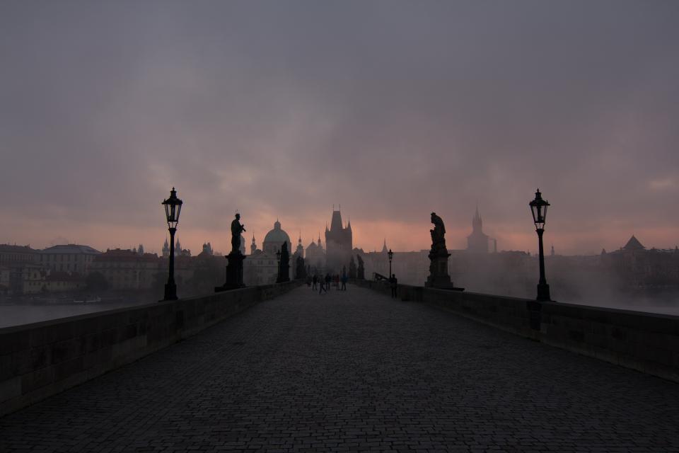 dark, fog, dusk, clouds, lamp posts, bridge, cobblestone, statues, buildings, city, architecture