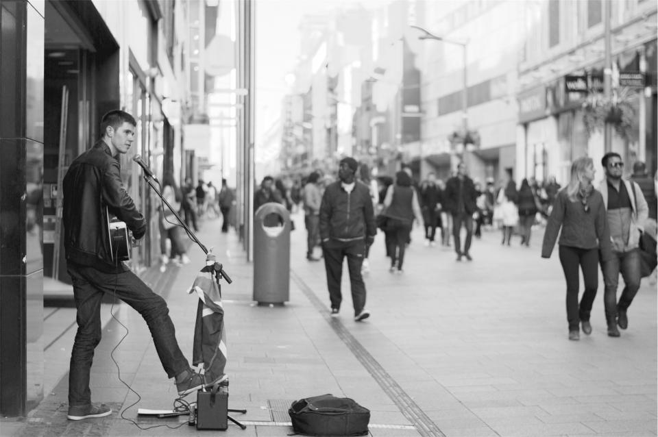 street performer, musician, music, guitar, musical instrument, people, pedestrians, crowd, buildings, city, architecture, urban, black and white
