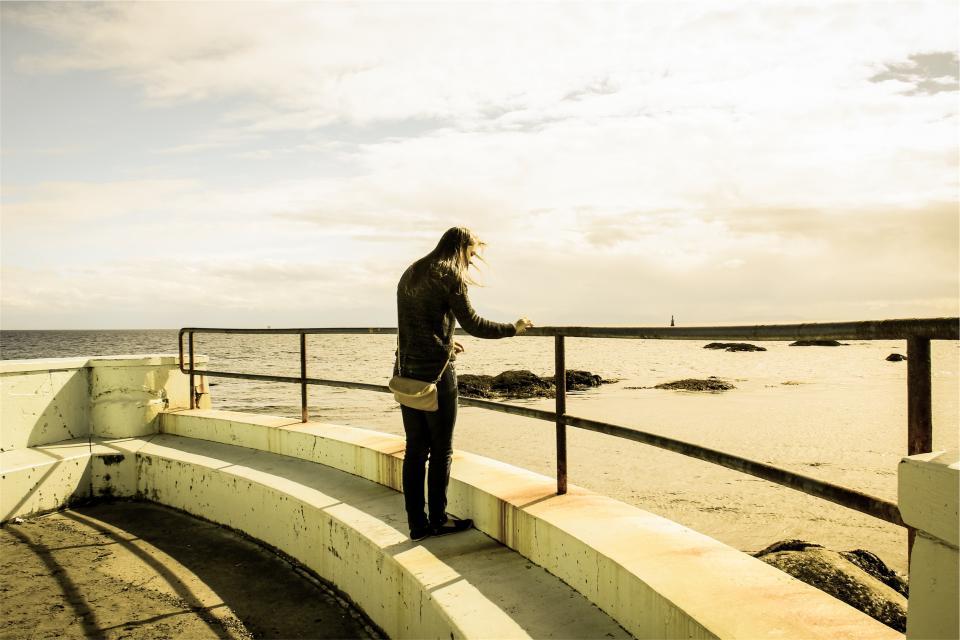 girl, woman, purse, steps, railing, beach, shore, wave, rocks, sky, people