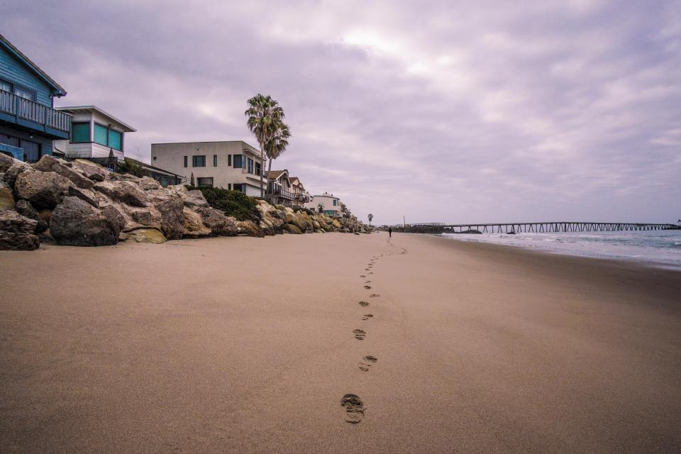 beach, houses, sand, footprints, beach, rocks, shore, purple, sky, clouds, ocean, sea